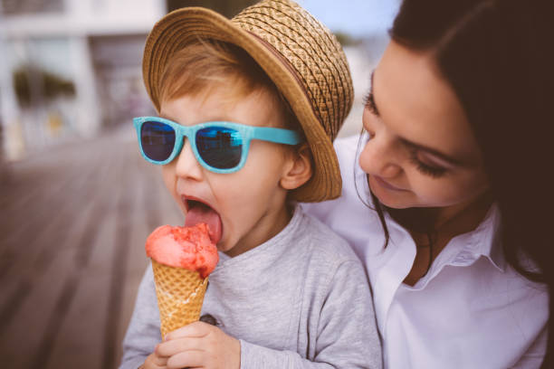 Cute young boy eating ice cream in his mother's arms stock photo