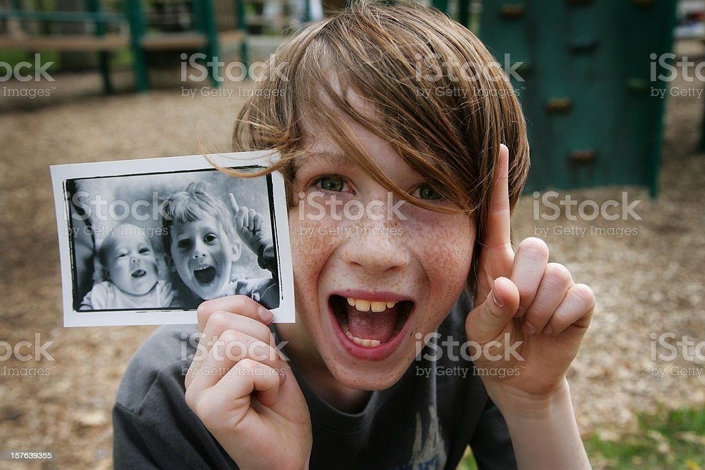 Cute Young Boy Holding Up Photo of Himself When Younger stock photo