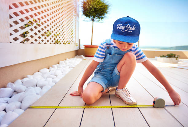 cute young boy, kid halps father with renovation of rooftop patio zone stock photo