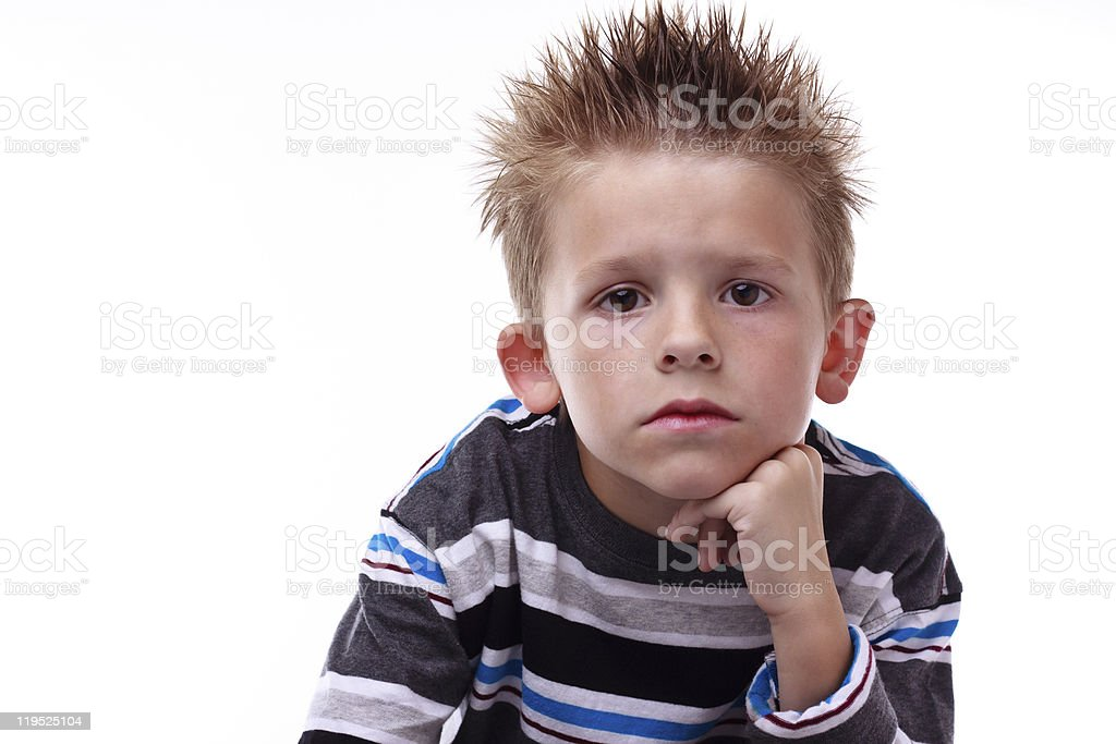 Cute young boy looking bored with hand on his chin royalty-free stock photo
