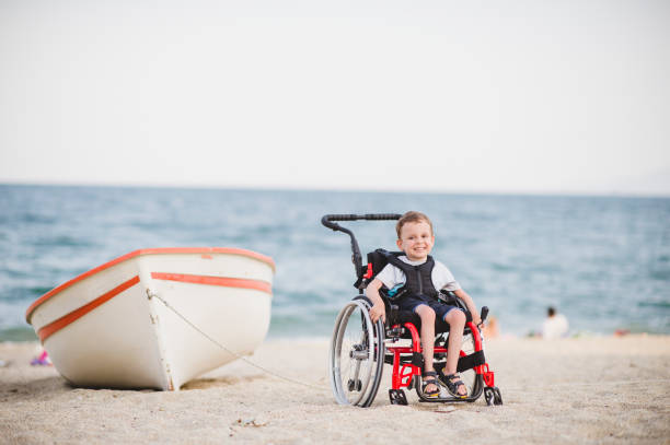 Cute young boy on the wheelchair by the sea Smiling young boy on the wheelchair by the sea sonderjylland stock pictures, royalty-free photos & images