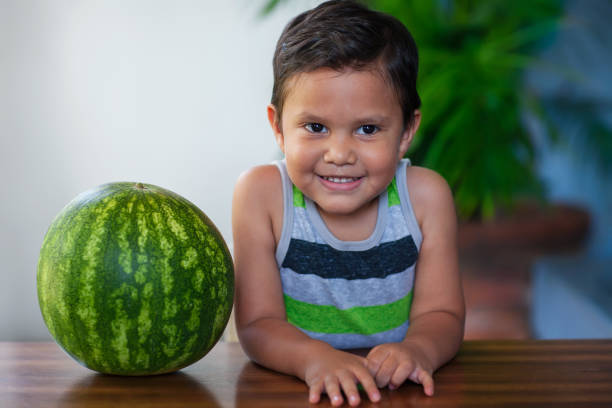 A cute young boy sitting next to a ripe watermelon he will be eating as part of a low-calorie and nutritious treat. stock photo