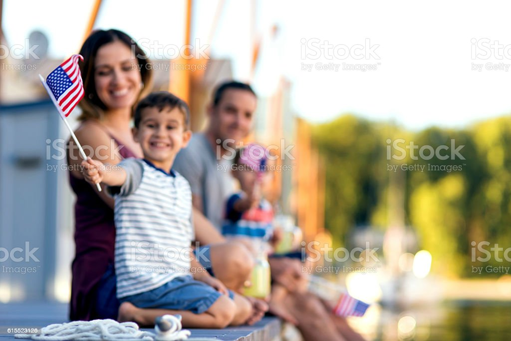Cute young boy waving a small American flag stock photo