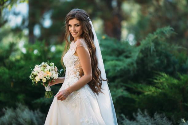niedliche junge braut mit langen haaren halten ihre hochzeit bouquet umfasst weiße rosen und andere blumen. schöne weiße hochzeit kleid. hübsches mädchen auf grüßen bäume hintergrund - hochzeitsfrisur boho stock-fotos und bilder