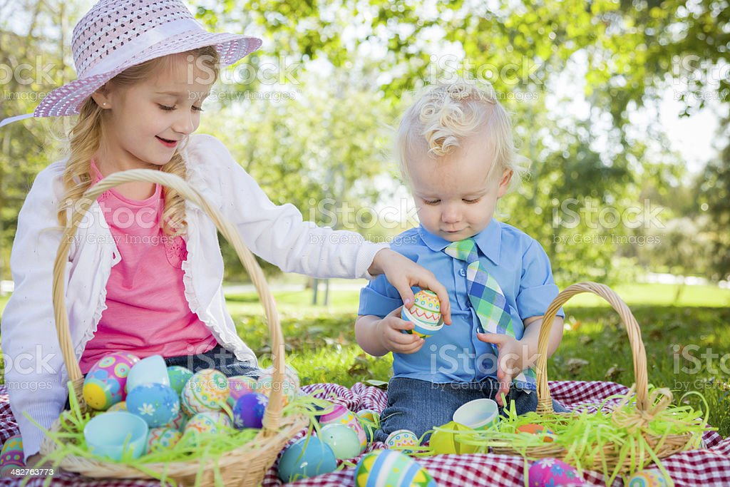Cute Young Brother and Sister Enjoying Their Easter Eggs Outside stock photo