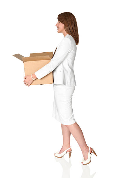 cute young businesswoman carrying a cardboard box - white suit stock photos and pictures