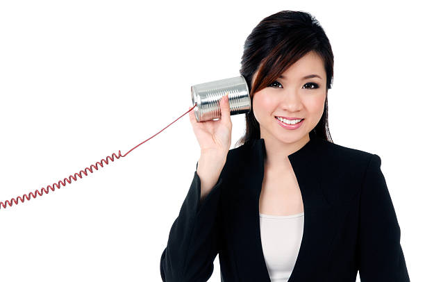 Süße junge Geschäftsfrau hören durch Dosentelefon – Foto