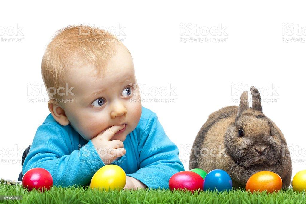 Carino giovane bambino con Coniglietto di Pasqua e uova su prato foto stock royalty-free