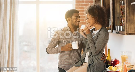 Happy morning together. Cute young african-american couple drinking coffee in cozy kitchen, panorama, copy space