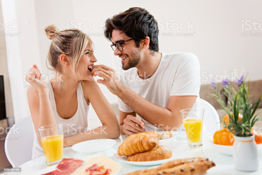 Cute young couple enjoying their breakfast together stock photo