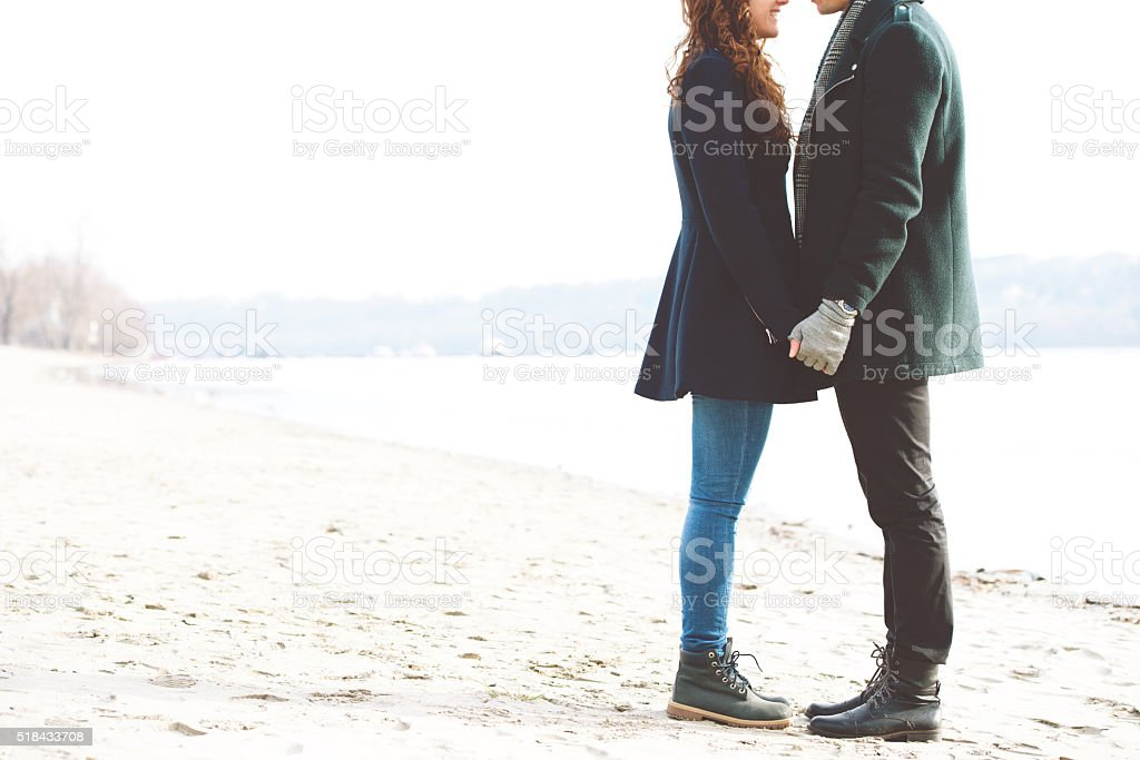 Cute young couple in love standing on the riverside stock photo