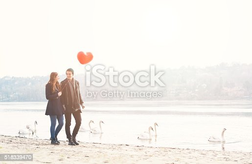 istock Cute young couple in love, walking at the riverside 518339470