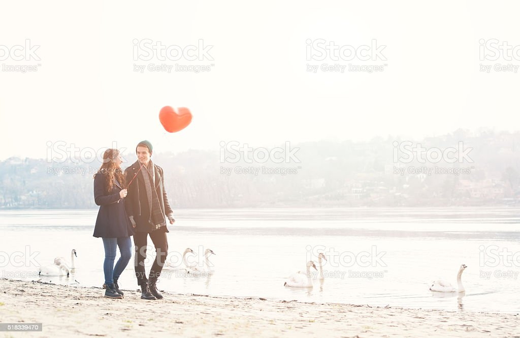Cute young couple in love, walking at the riverside stock photo