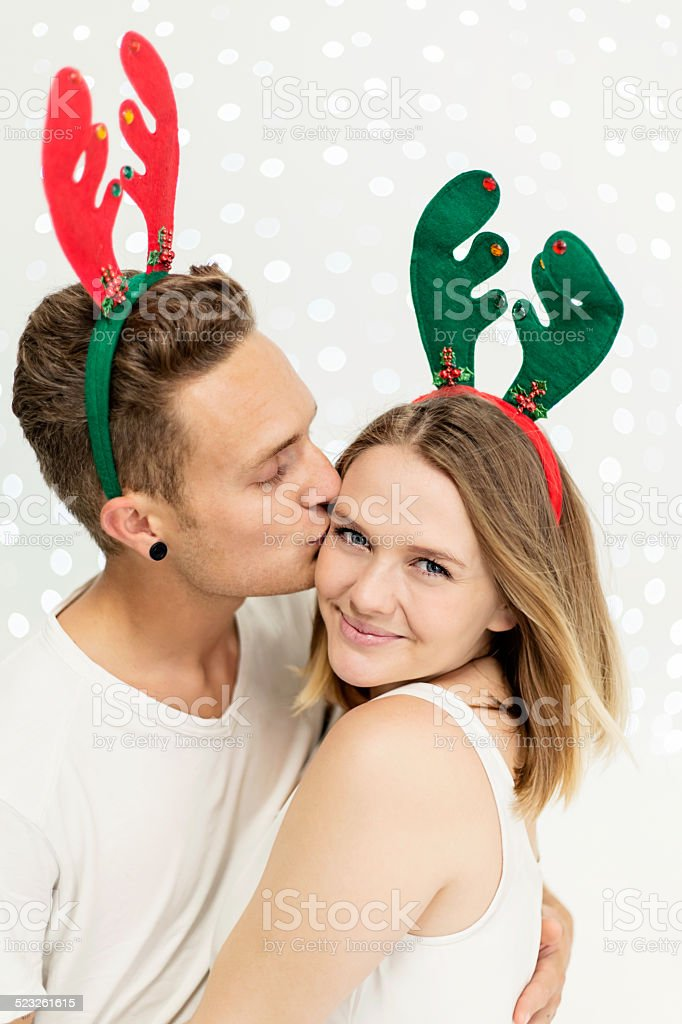 Cute young couple in reindeer headbands embrace, celebrating Christmas stock photo