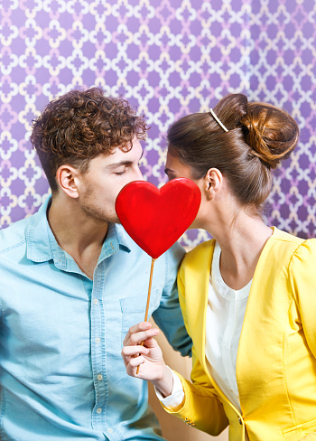 518335358 istock photo Cute young couple kissing behind a heart 464554198