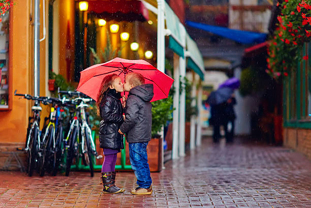cute young couple kissing under the rain - little girls little boys kissing love stock photos and pictures