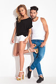 Cute young couple leaning on a white wall while looking at the camera.