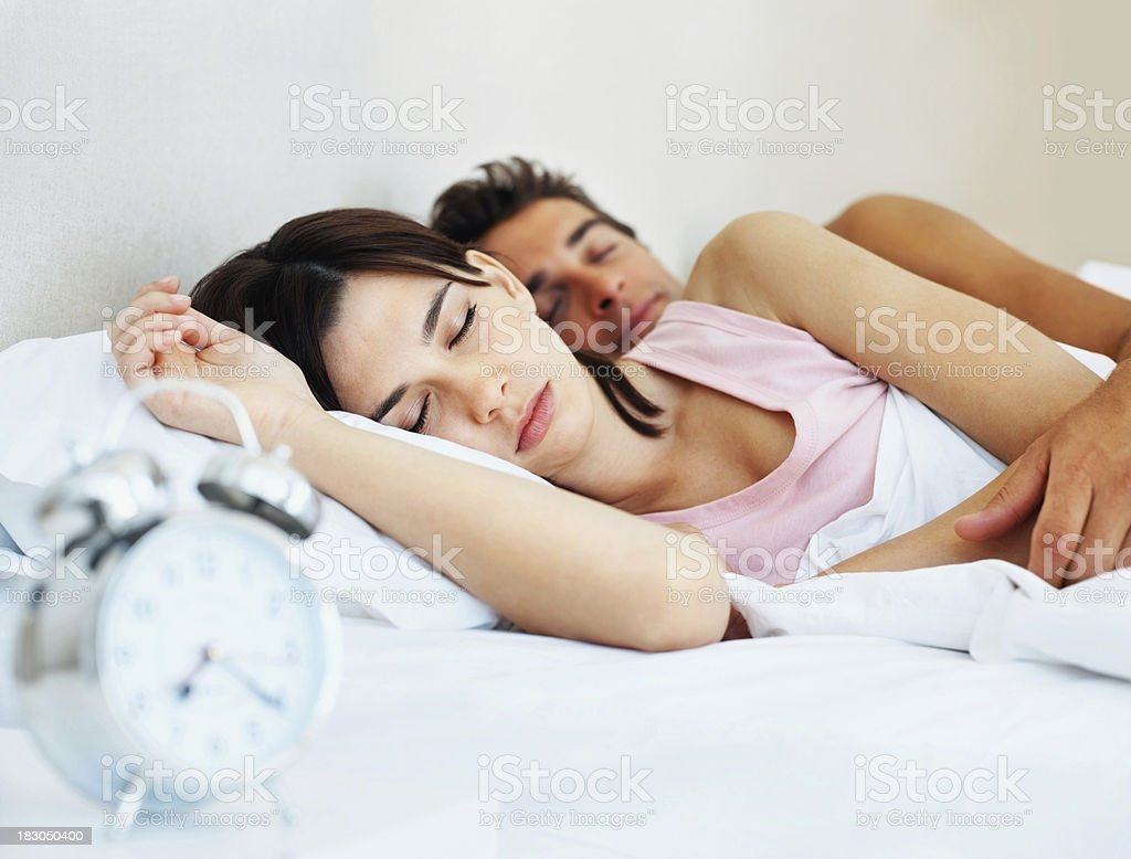 Cute young couple sleeping together on bed at home royalty-free stock photo