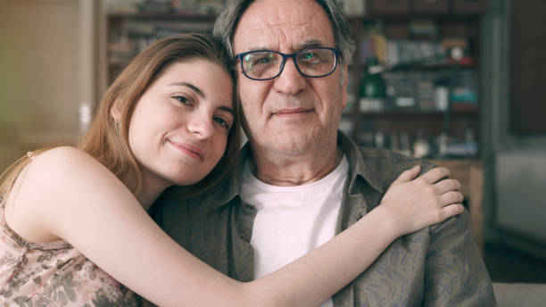 Cute young daughter embracing her father with love stock photo