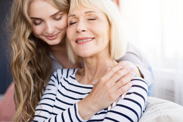 linda joven hija abrazando a su madre con amor - hija fotografías e imágenes de stock