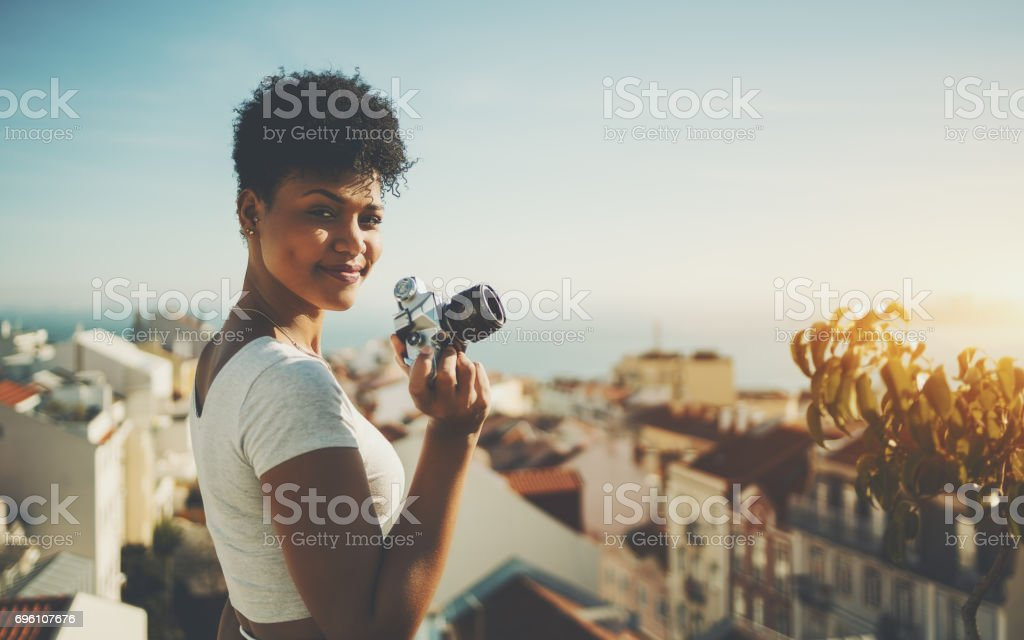 Cute young female journalist with vintage film camera stock photo