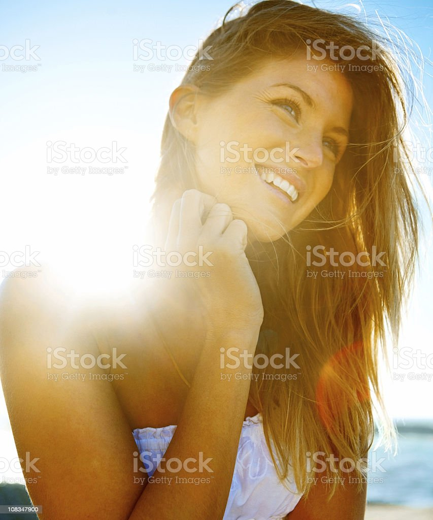 Cute young female looking away against sky stock photo