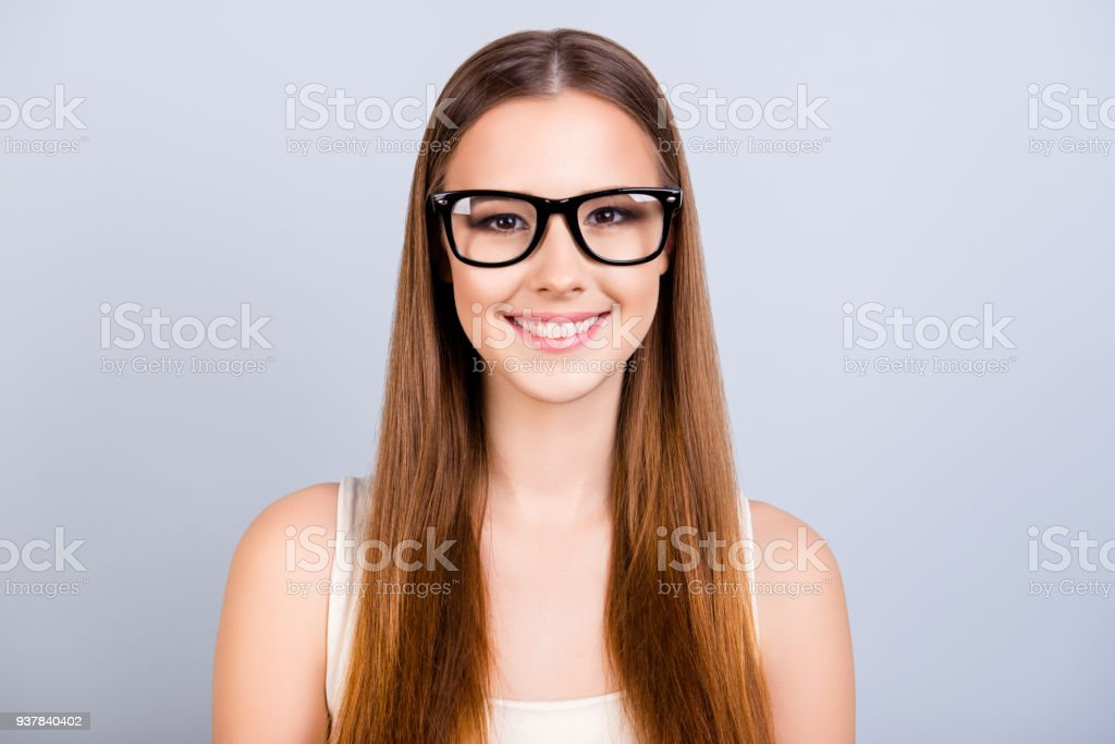 6d2787c8894b6 Cute young female student is in a stylish black glasses, wearing casual  singlet, smiling, standing on pure light background with long hair - Stock  image .