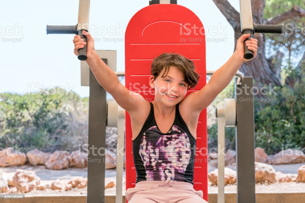 Cute young girl exercising arms and chest on gym machine outdoors. stock photo