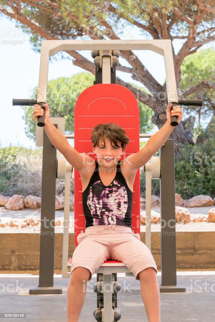 Cute young girl exercising upper body on gym machine outdoors. royalty-free stock photo