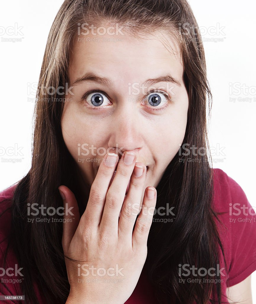 Cute young girl, hand over mouth, with big eyes stock photo
