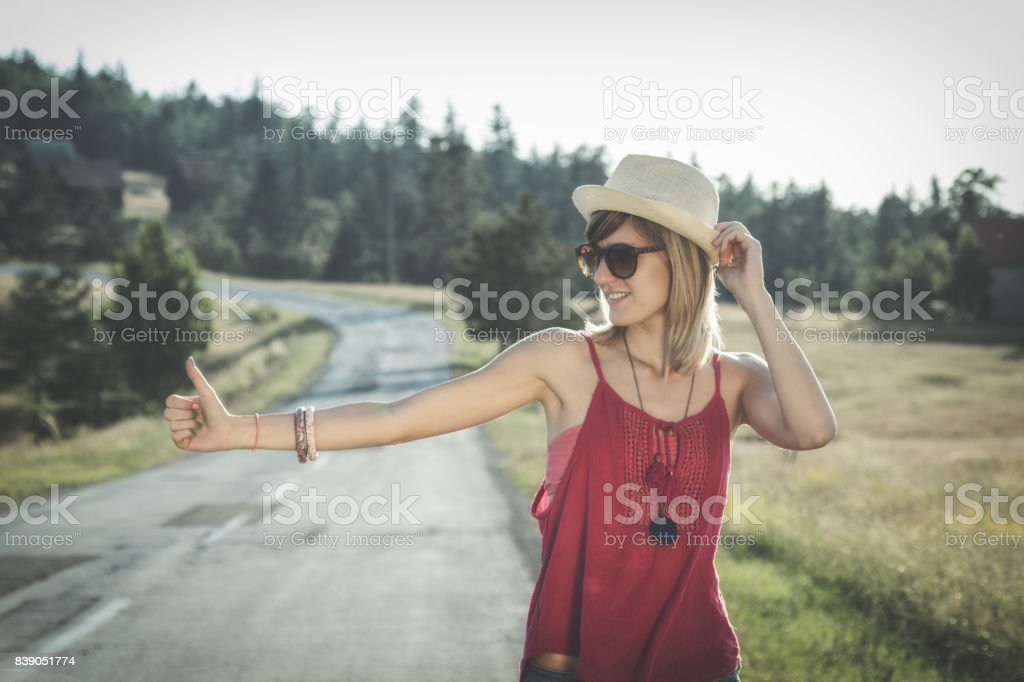 Cute young girl hitchhiking on the countryside road. stock photo