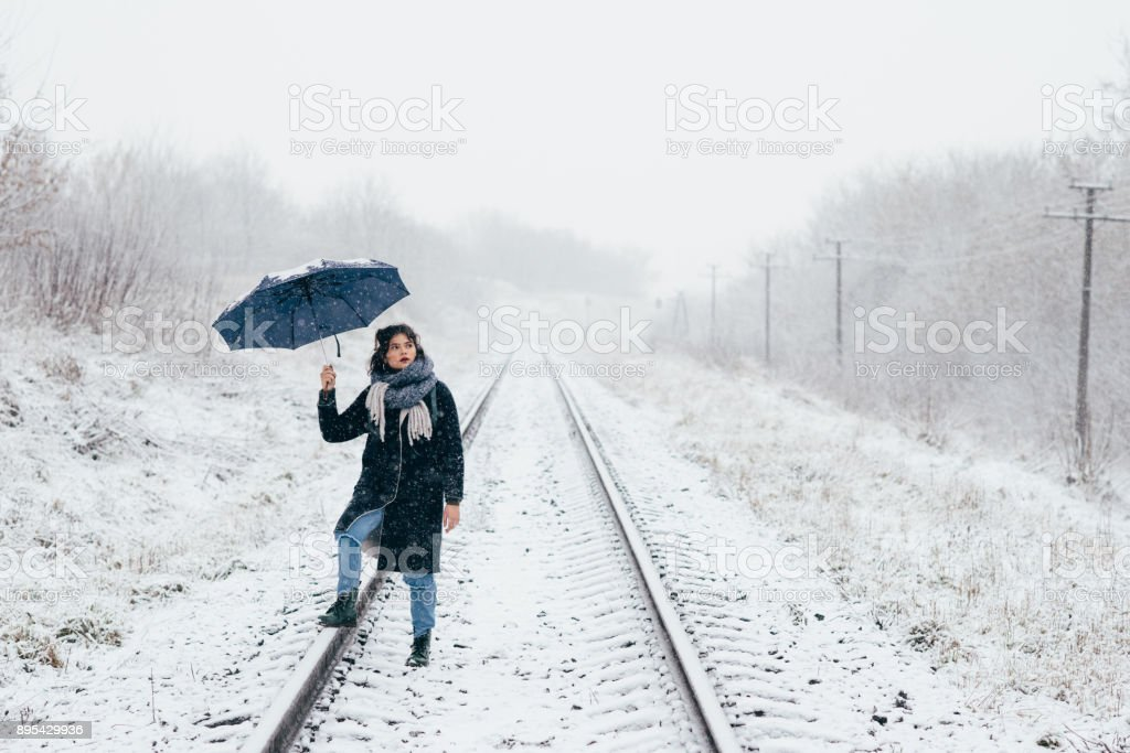 A cute young girl holds umbrella in the hands of the winter season stock photo