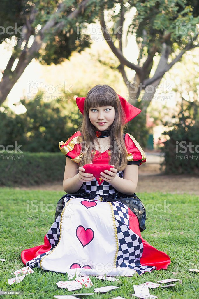 Cute young girl in a card's queen costume stock photo