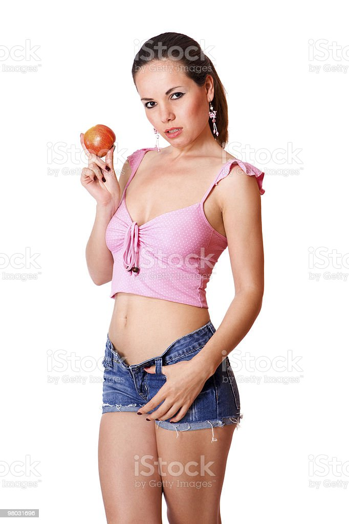 Cute young girl in blue shorts holding an apple isolated stock photo