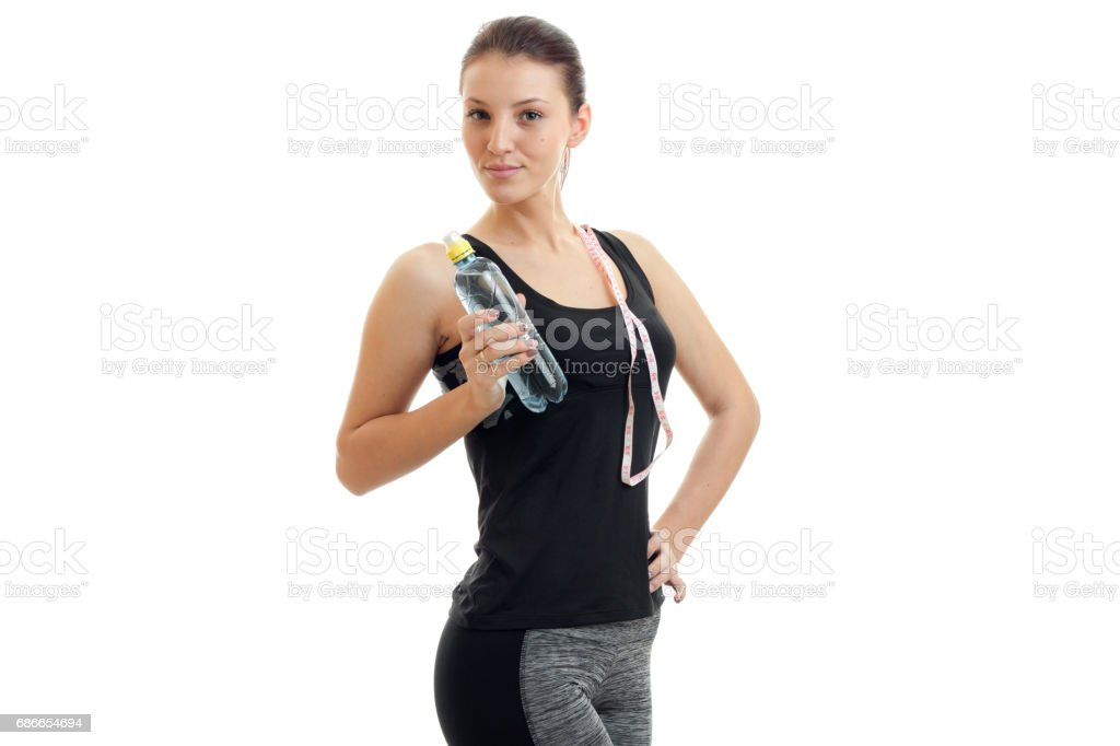 cute young girl in fitness black t-shirt looks away and keeps the shoulder strap and a bottle of water in hand royalty-free stock photo