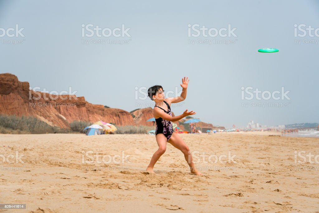 Cute young girl in swimsuit standing on a beach by the sea throwing frisbee. royalty-free stock photo