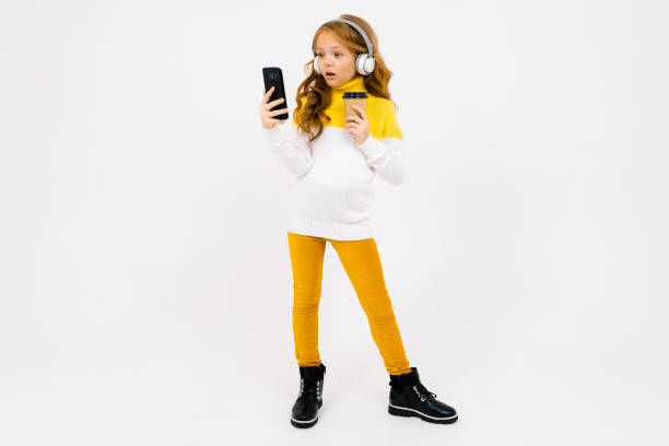 cute young girl in white headphones looks at the phone and holds a glass on a white background stock photo