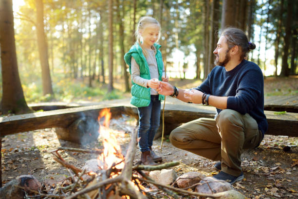 Cute young girl learning to start a bonfire. Father teaching her daughter to make a fire. Child having fun at camp fire. Camping with kids in fall forest. stock photo