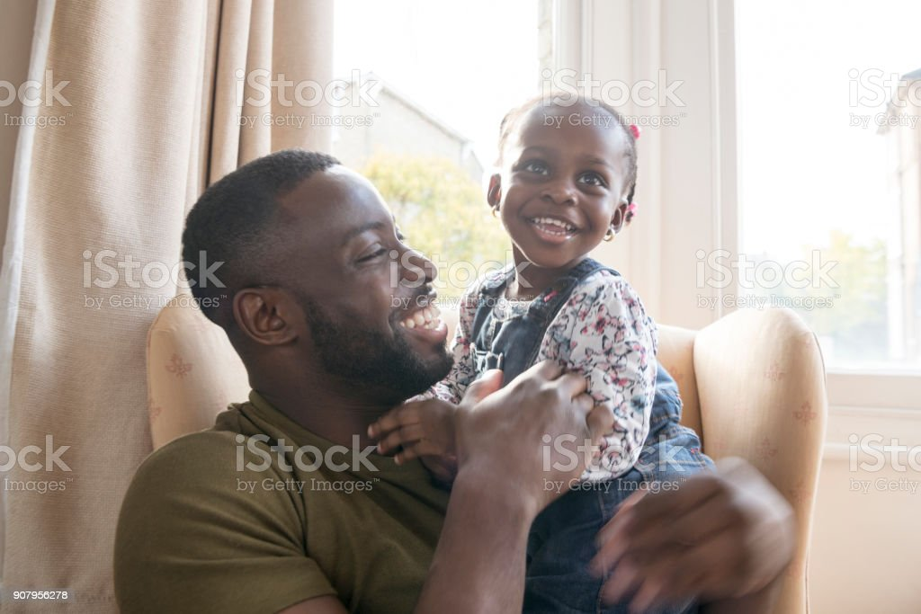 Cute young girl on father's lap smiling and looking away stock photo