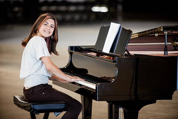 Cute Young Girl Playing Piano stock photo