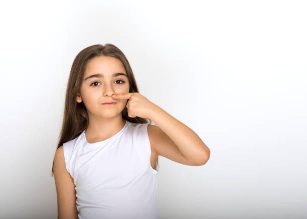 Süße junge Mädchen setzen Finger auf Gesicht – Foto