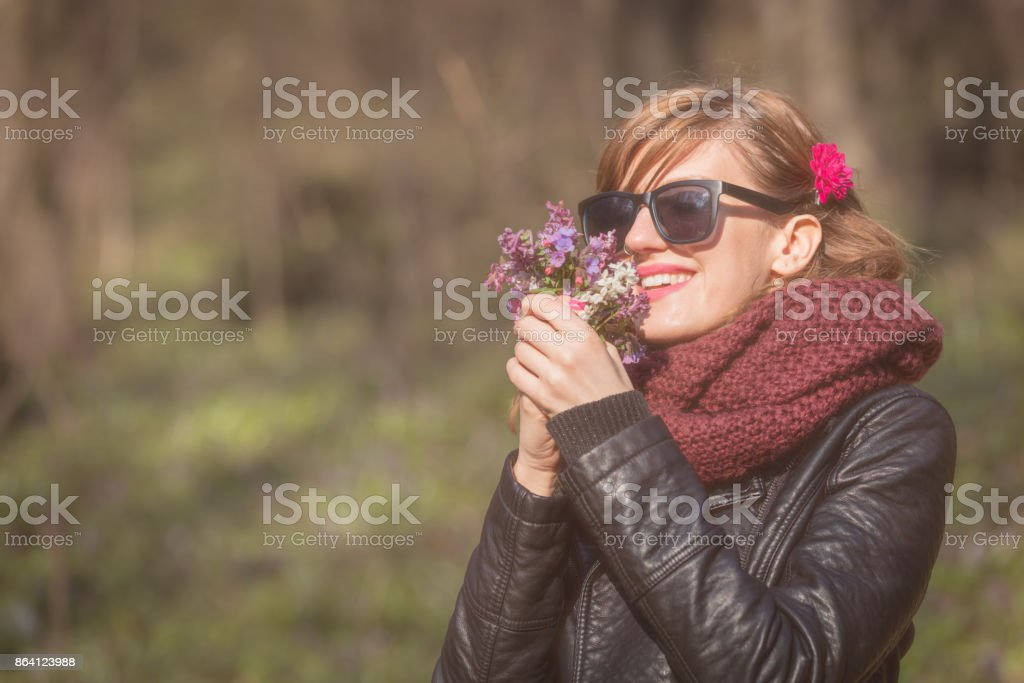 Cute young girl smelling nice bouquet of flowers in nature. royalty-free stock photo