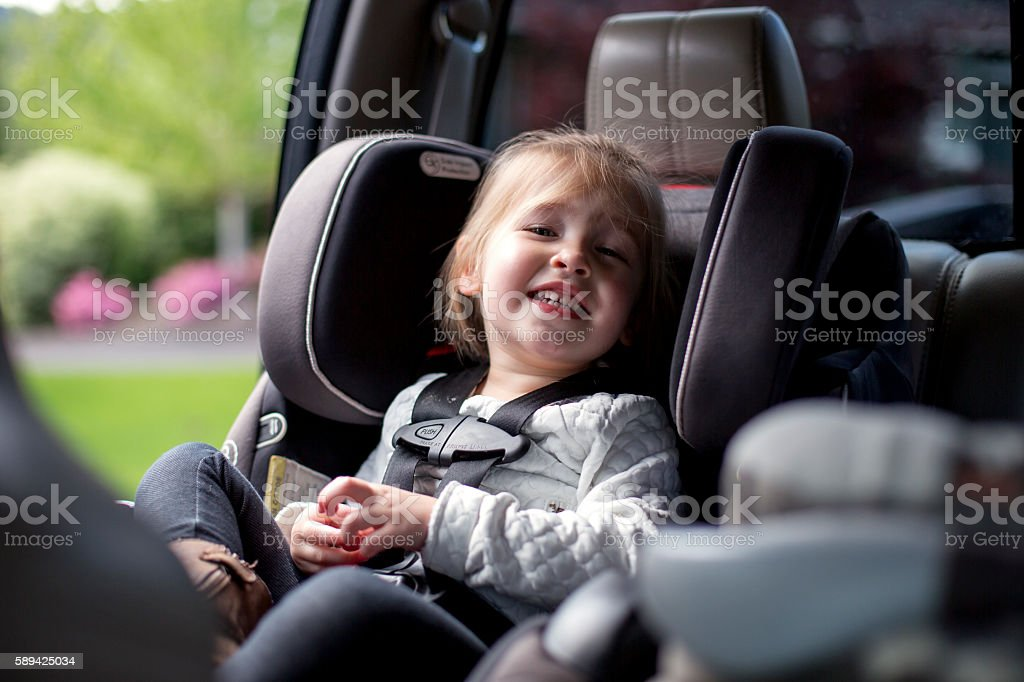 Cute young girl smiling in her car seat stock photo