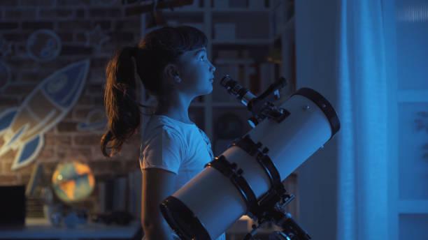 Süße junge Mädchen Sternenhimmel in der Nacht mit einem Teleskop sucht sie entfernt: Phantasie und Kindheit Konzept – Foto
