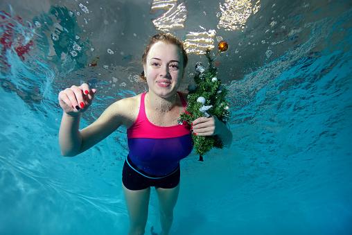 かわいい若い女の子水中プールで泳ぎますおもちゃでクリスマス ツリー ...