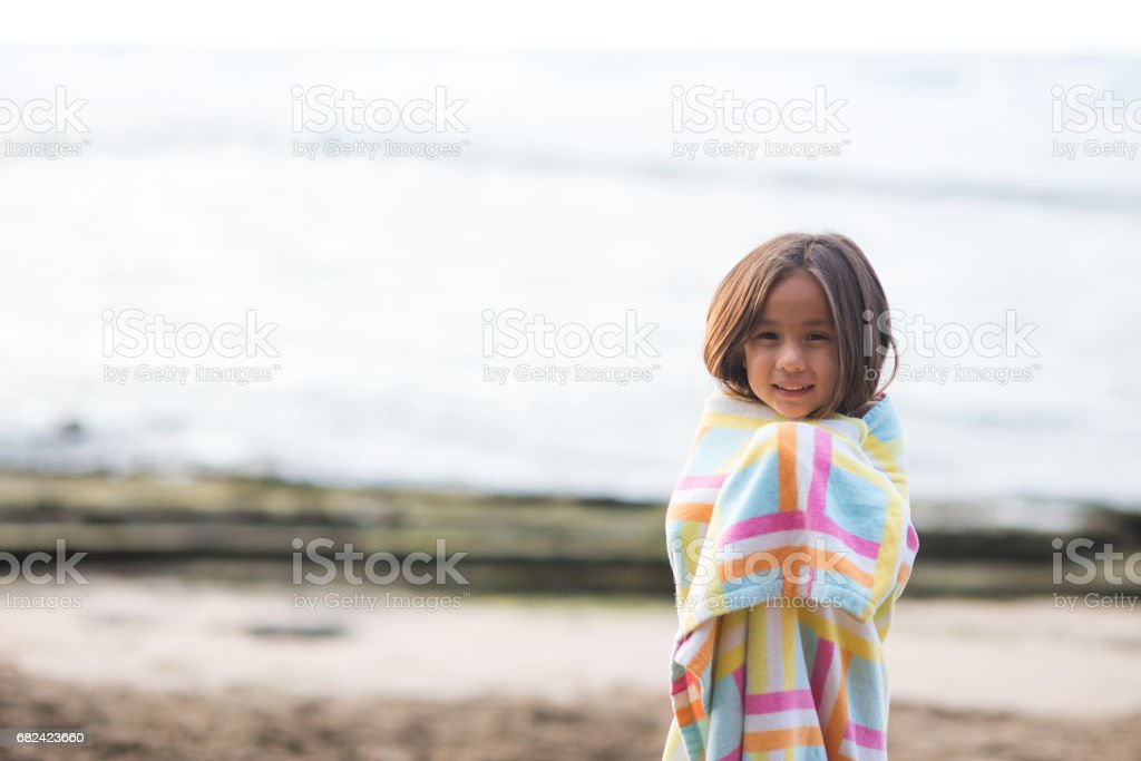 Cute young girl wraps herself up in towel after a surfing session royalty-free stock photo