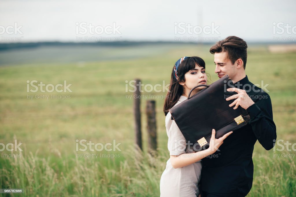 dee0b9e56f72 A cute young guy stands next to a pretty girl in whose hands a business bag  - Stock image .