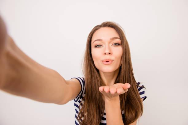 linda joven soñando feliz en camiseta a rayas aislado sobre fondo blanco tomando una selfie y dando aire-kiss - video modelo fotografías e imágenes de stock