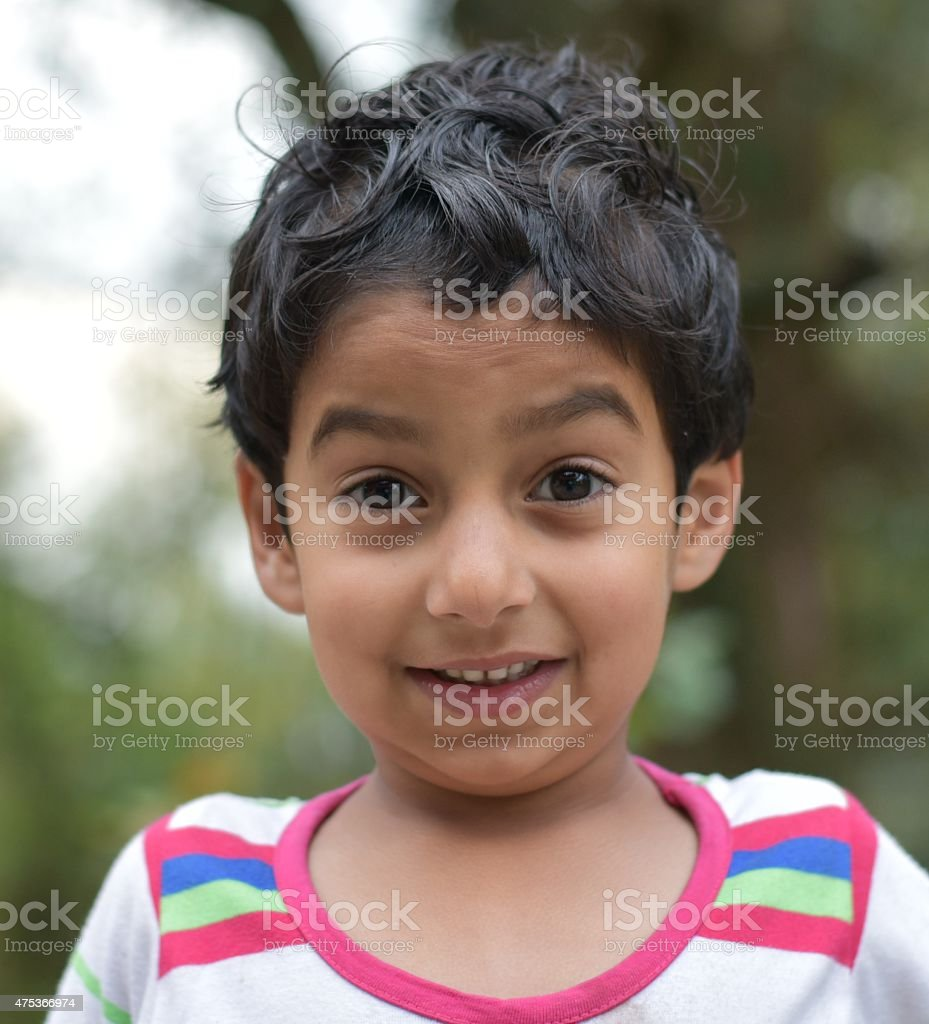cute young indian baby girl smiling with soft green backdrop stock