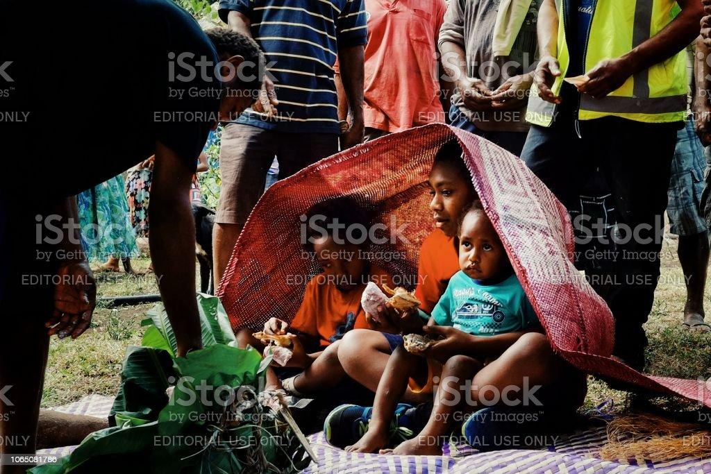 niedliche kleine Kinder akzeptieren Angebote wie Taro, gewebte Yam, traditionelle Matten für ihr Ritual der Beschneidung – Foto
